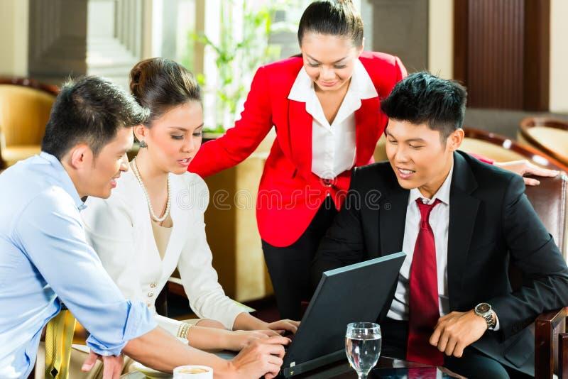 Hombres de negocios asiáticos en la reunión en pasillo del hotel foto de archivo
