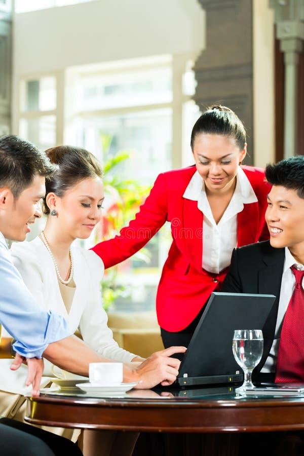 Hombres de negocios asiáticos en la reunión en pasillo del hotel fotos de archivo libres de regalías