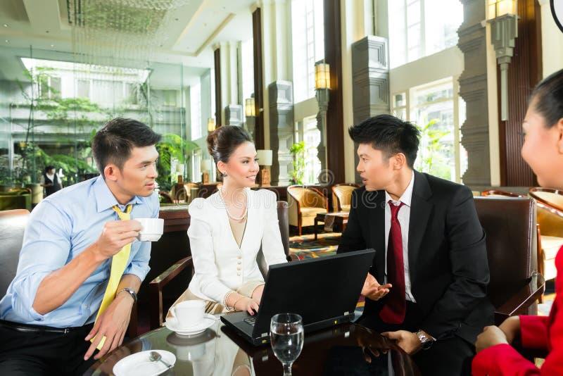 Hombres de negocios asiáticos en la reunión en pasillo del hotel foto de archivo libre de regalías