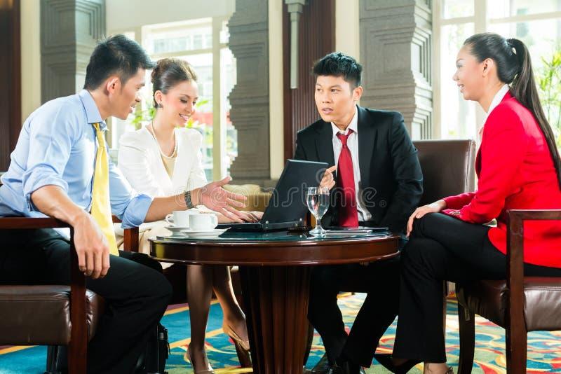 Hombres de negocios asiáticos en la reunión en pasillo del hotel imagen de archivo