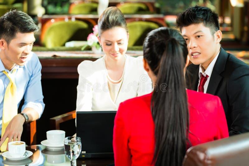 Hombres de negocios asiáticos en la reunión en pasillo del hotel imágenes de archivo libres de regalías
