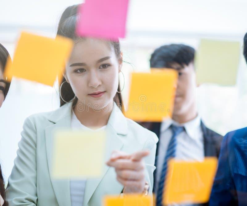 Hombres de negocios asiáticos que discuten y que planean usando el frente de la nota de post-it del vidrio foto de archivo libre de regalías