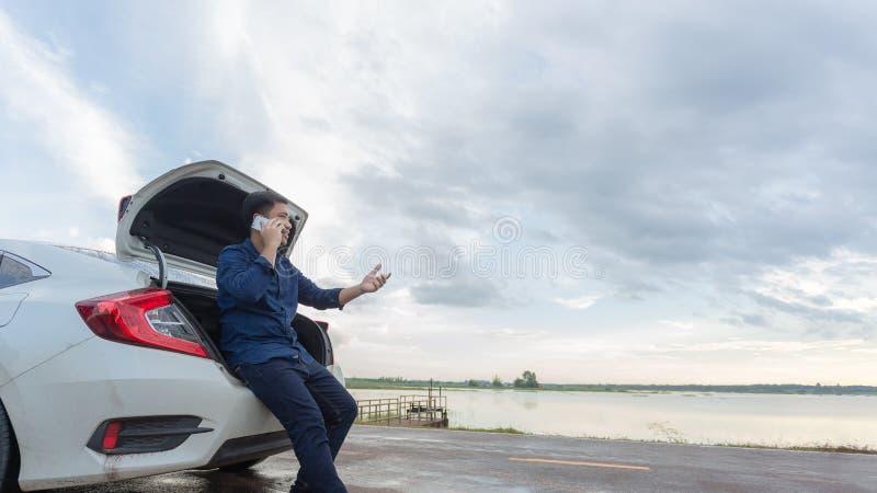 Hombres de negocios asiáticos que hablan en un teléfono celular por un coche quebrado en Cou fotos de archivo libres de regalías