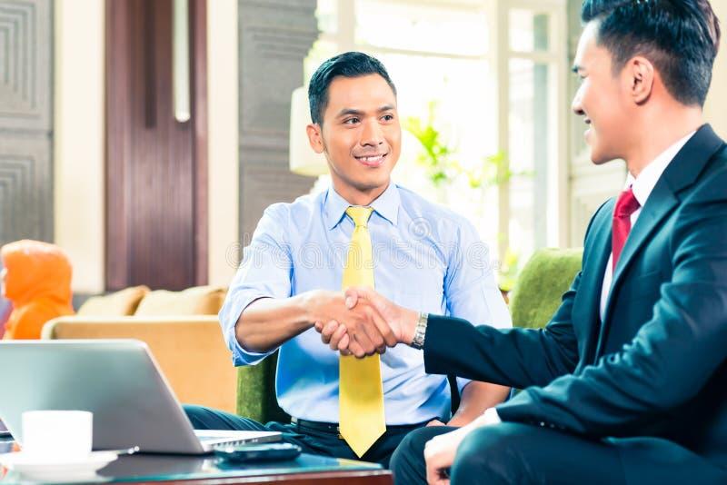 Hombres de negocios asiáticos que tienen reunión foto de archivo