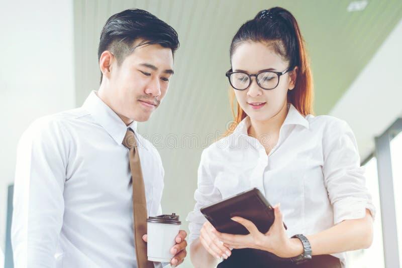 Hombres de negocios asiáticos que usan la tableta digital al aire libre después del trabajo B imagenes de archivo