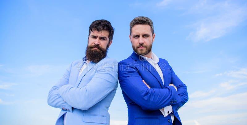 Hombres de negocios barbudos que presentan con confianza Los hombres de negocios colocan el fondo del cielo azul Perfeccione en c imágenes de archivo libres de regalías