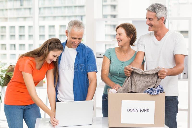 Hombres de negocios casuales que clasifican donaciones imagen de archivo libre de regalías
