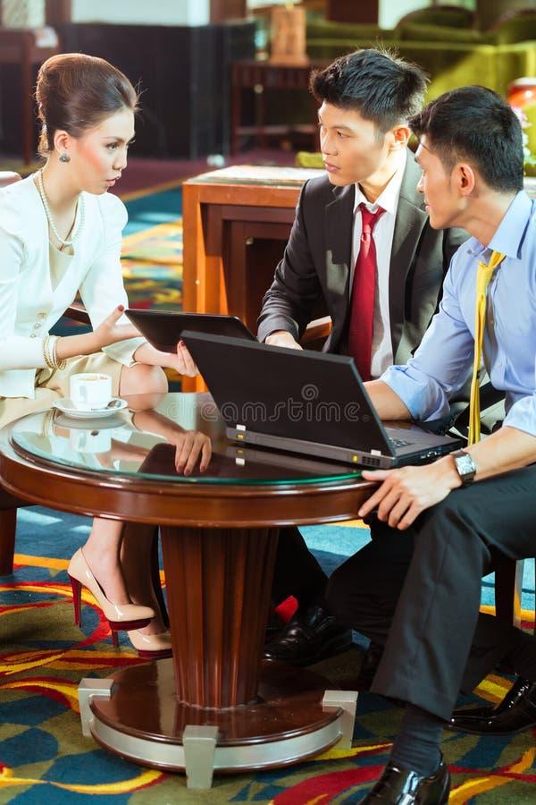Hombres de negocios chinos en la reunión en pasillo del hotel imagen de archivo