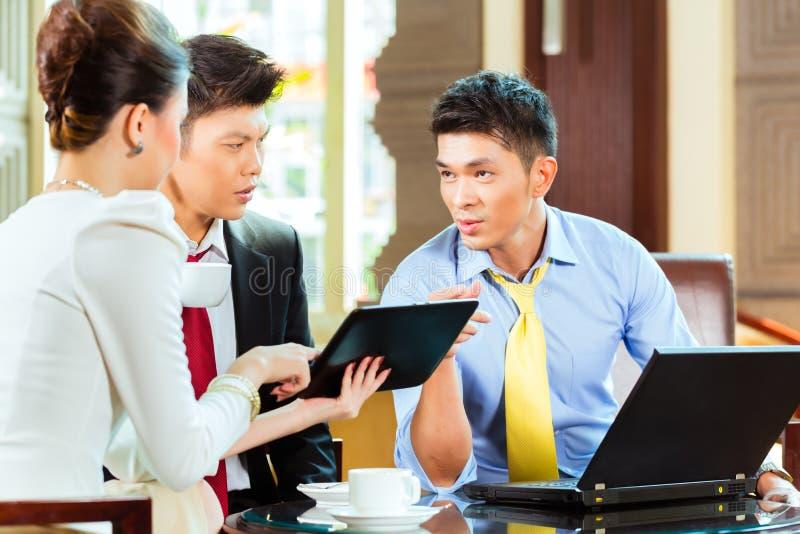 Hombres de negocios chinos en la reunión en pasillo del hotel fotografía de archivo