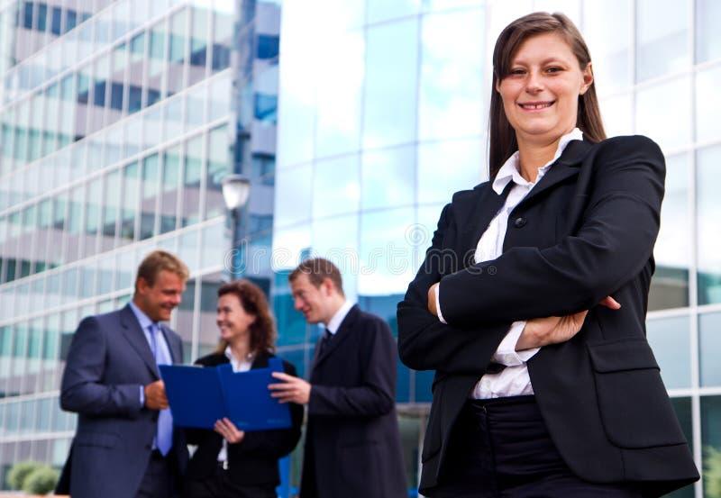 Hombres de negocios con el líder de la empresaria en primero plano foto de archivo