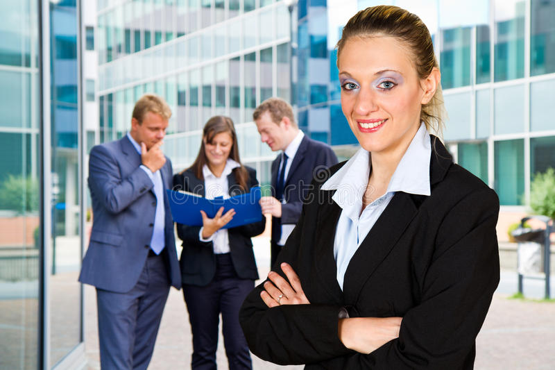 Hombres de negocios con el líder de la empresaria en primero plano imagen de archivo
