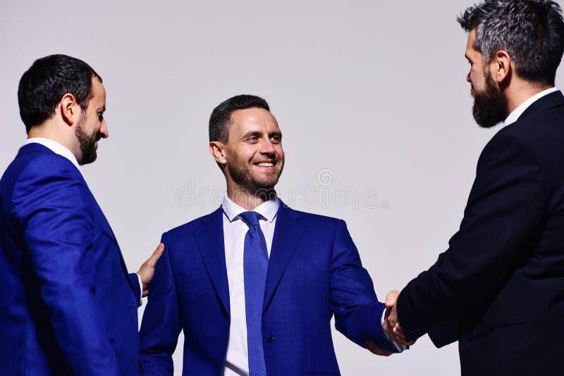 Hombres de negocios con las caras felices en desgaste formal en fondo gris imagen de archivo libre de regalías