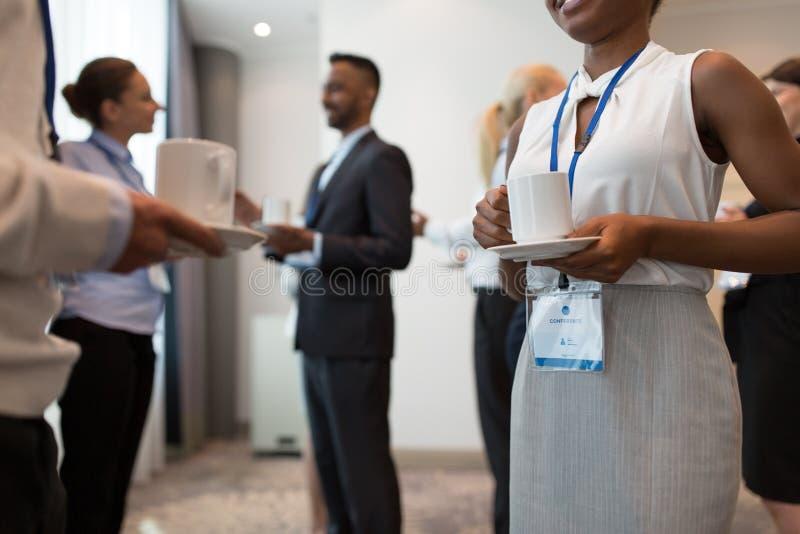 Hombres de negocios con las insignias y el caf? de la conferencia fotografía de archivo libre de regalías
