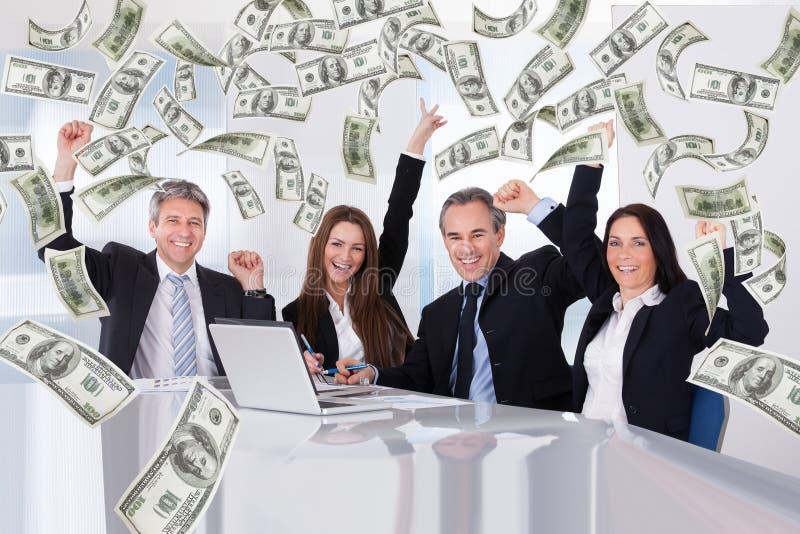 Hombres de negocios con lluvia del dinero en la sala de conferencias fotografía de archivo