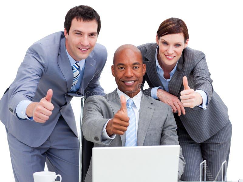 Hombres de negocios con los pulgares para arriba que miran una computadora portátil imagen de archivo