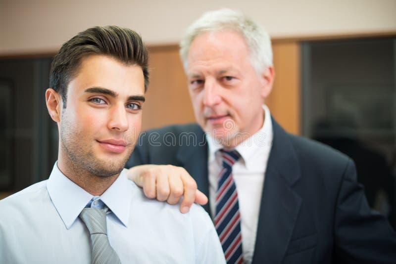 Hombres de negocios confiados delante de su jefe fotos de archivo