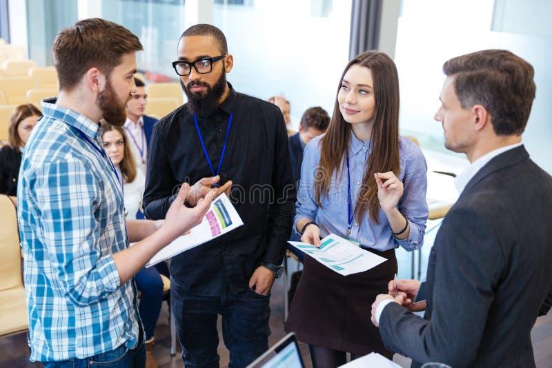 Hombres de negocios confiados que colocan y que discuten informe financiero en oficina imagenes de archivo