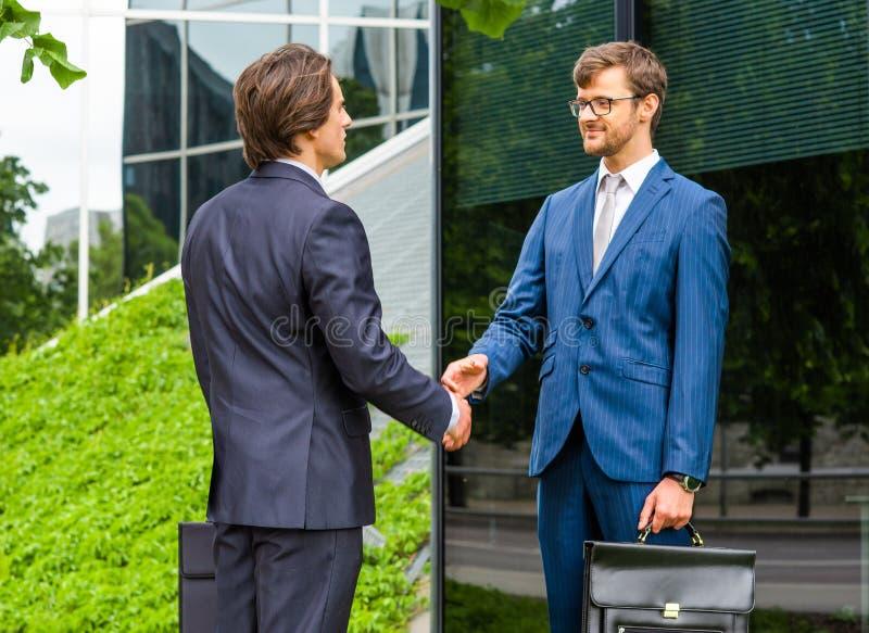 Hombres de negocios confiados que hablan delante del edificio de oficinas moderno Hombre de negocios y su colega Actividad bancar fotos de archivo libres de regalías