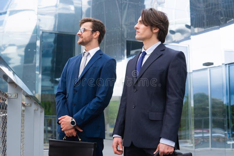 Hombres de negocios confiados que hablan delante del edificio de oficinas moderno Hombre de negocios y su colega Actividad bancar imagenes de archivo