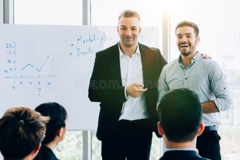 Hombres de negocios contemporáneos que hacen la presentación para los colegas imagen de archivo libre de regalías