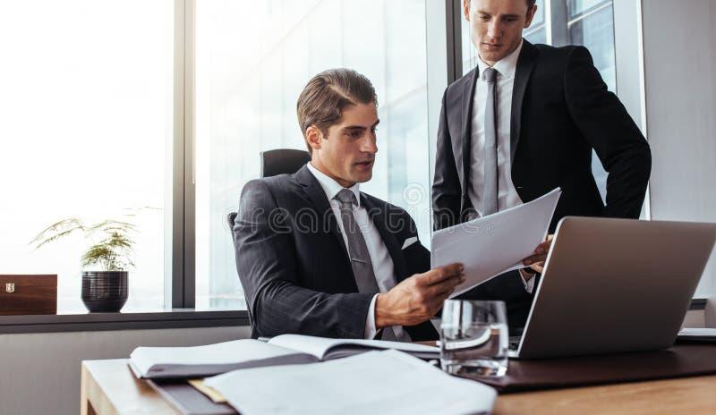 Hombres de negocios corporativos que leen los papeles en oficina fotografía de archivo libre de regalías