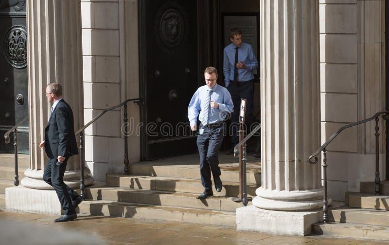 Hombres de negocios corridos hacia fuera de las puertas del Banco de Inglaterra imagenes de archivo