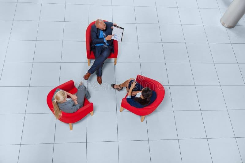 Hombres de negocios de la reunión de grupo que discute el plan que comunica, opinión del proyecto del documento de ángulo superio foto de archivo