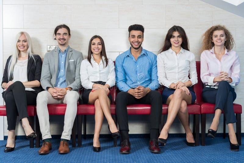 Hombres de negocios de la reunión de grupo que se sienta en la línea cola, reclutamiento para Job Interview que espera de la much fotografía de archivo libre de regalías