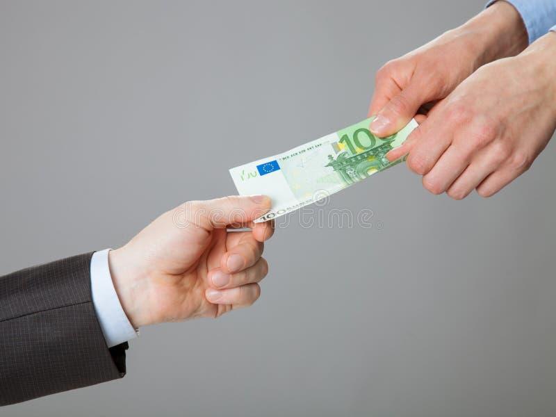 Hombres de negocios de las manos que intercambian el dinero imagen de archivo