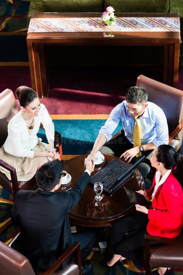 Hombres de negocios del apretón de manos en oficina imagen de archivo