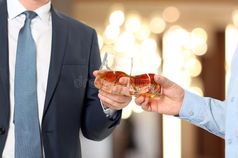 Hombres de negocios del evento del día de fiesta que se animan con el whisky imagen de archivo