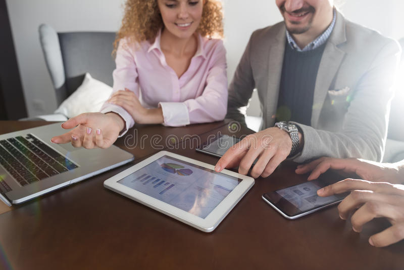 Hombres de negocios del informe de Team Group Discussing Financial Diagram sobre los empresarios de la pantalla de la tableta que fotografía de archivo