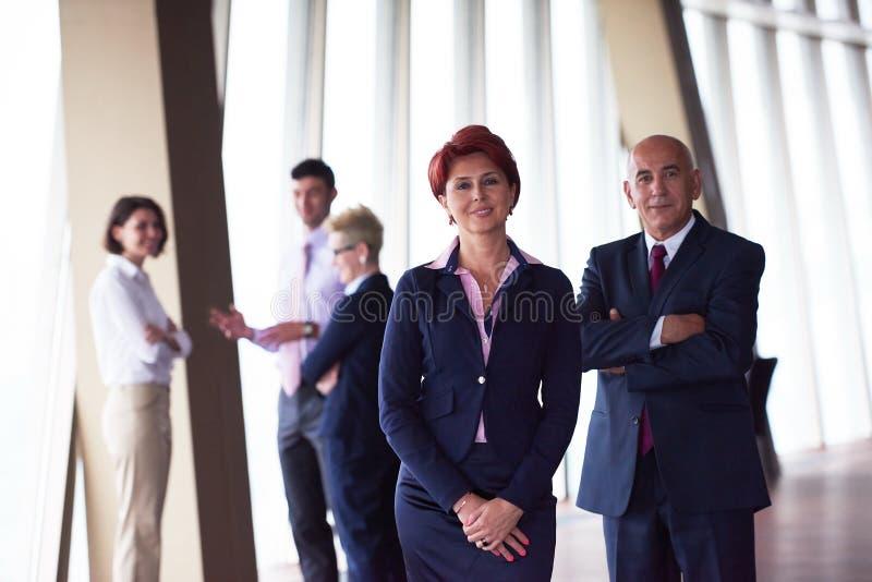 Hombres de negocios diversos del grupo con la mujer del redhair en frente imagen de archivo libre de regalías