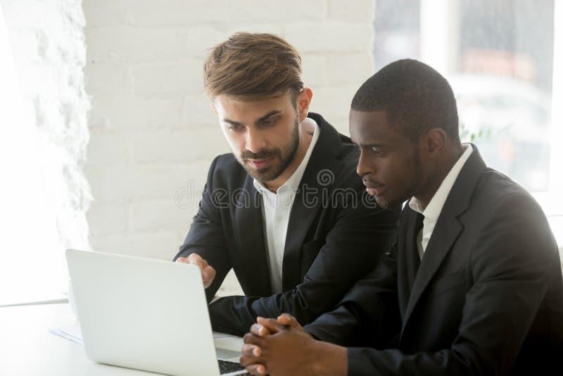 Hombres de negocios diversos en trajes que analizan el proyecto en línea junto o foto de archivo