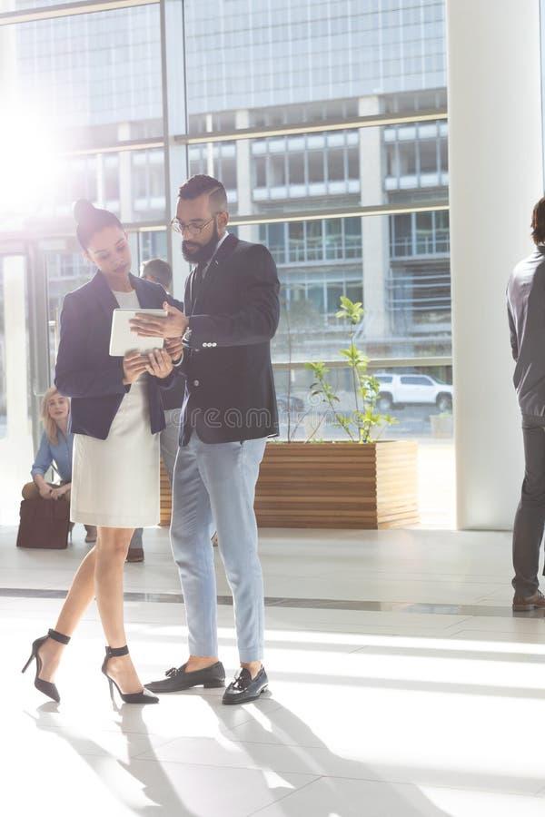Hombres de negocios diversos que miran y que discuten sobre la tableta digital en oficina del pasillo fotos de archivo