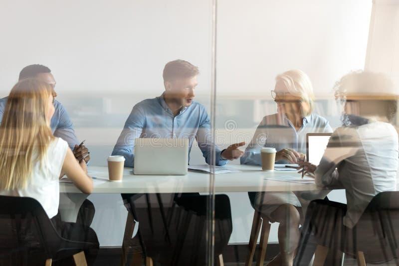 Hombres de negocios diversos que negocian en la tabla detrás de la puerta de cristal cerrada imagen de archivo libre de regalías