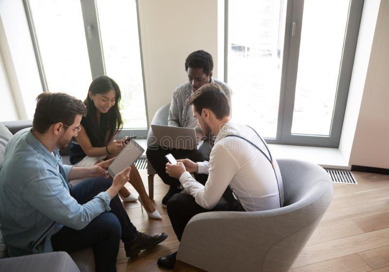 Hombres de negocios diversos que usan los dispositivos en el encuentro en oficina foto de archivo libre de regalías