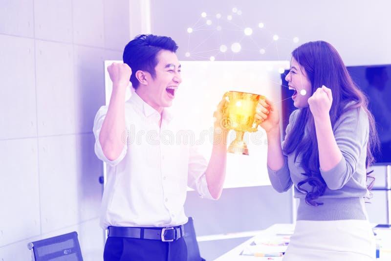 Hombres de negocios elegantes asiáticos de la felicidad joven que llevan a cabo premios del trofeo del oro juntos después de eq imagenes de archivo