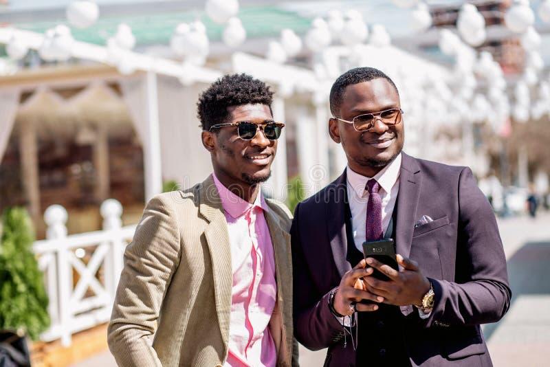Hombres de negocios elegantes sonrientes que colocan el teléfono celular al aire libre andusing imágenes de archivo libres de regalías