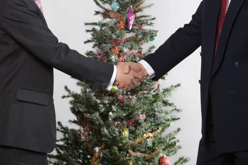 Hombres de negocios en árbol de navidad delantero fotografía de archivo libre de regalías