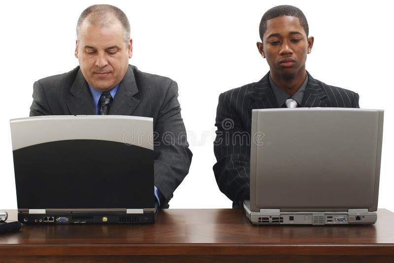 Hombres de negocios en el escritorio con las computadoras portátiles fotos de archivo
