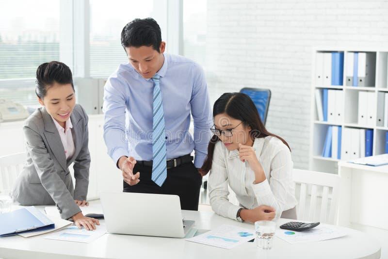 Hombres de negocios en el ordenador portátil imagen de archivo