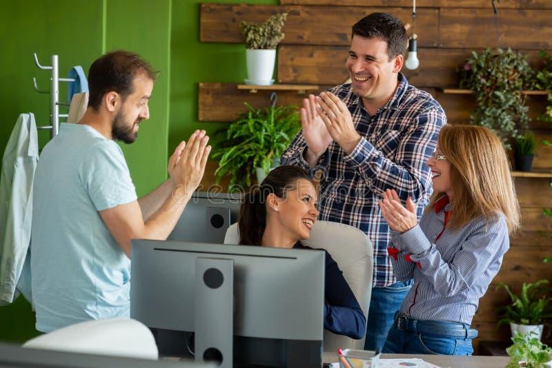 Hombres de negocios en la oficina acogedora que aplaude en el éxito del nuevo proyecto fotos de archivo