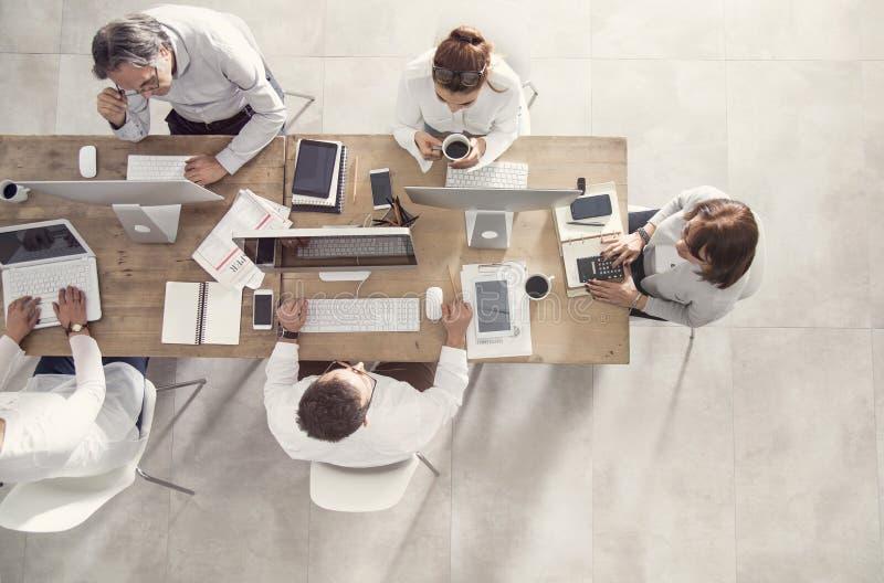 Hombres de negocios en la opinión de sobremesa de la reunión foto de archivo libre de regalías