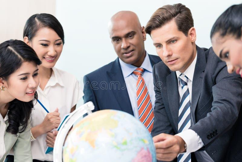 Hombres de negocios en la reunión de la estrategia que discuten nuevos mercados imagen de archivo libre de regalías