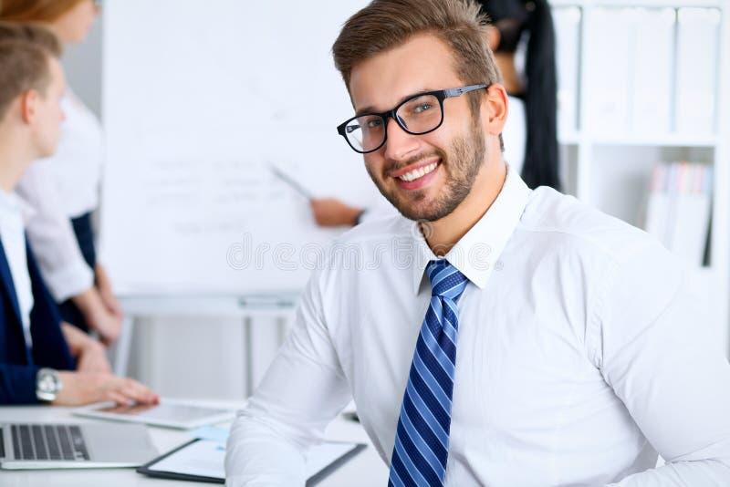 Hombres de negocios en la reunión en oficina Céntrese en los vidrios que llevan sonrientes alegres del hombre barbudo Conferencia fotos de archivo