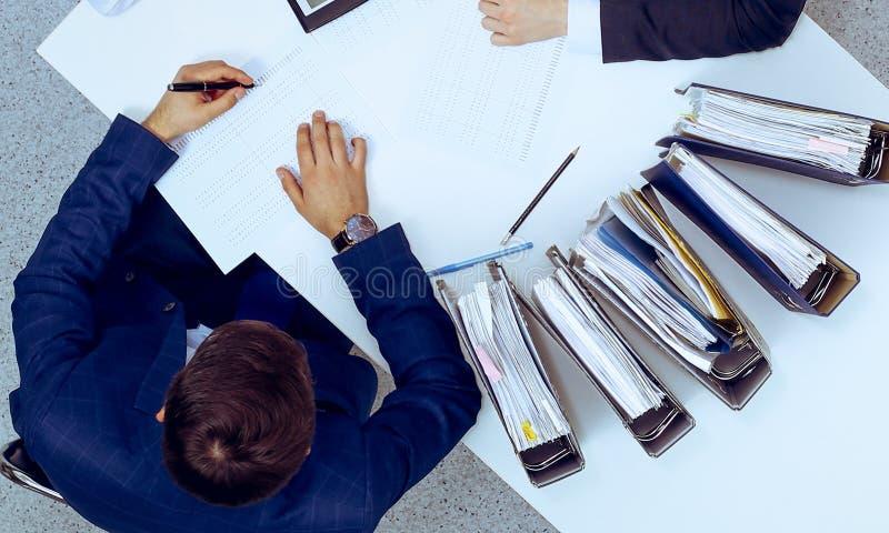 Hombres de negocios en la reuni?n, visi?n desde arriba Contable o inspector financiero que hace informe, el cálculo o la comproba fotos de archivo libres de regalías