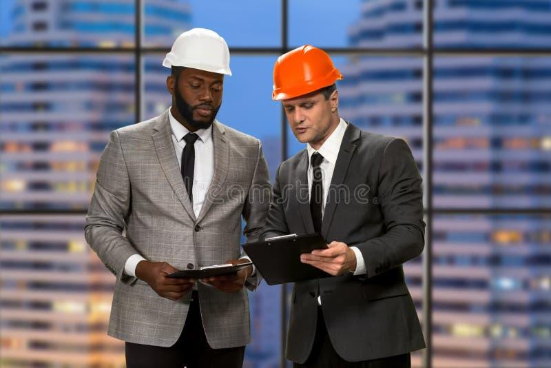 Hombres de negocios en los cascos que sostienen los tableros foto de archivo libre de regalías