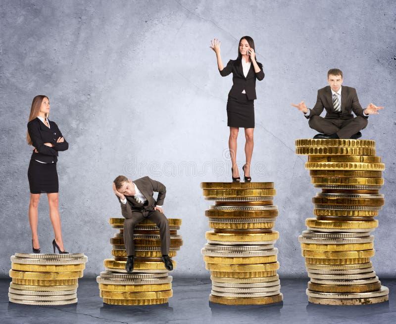 Hombres de negocios en monedas foto de archivo