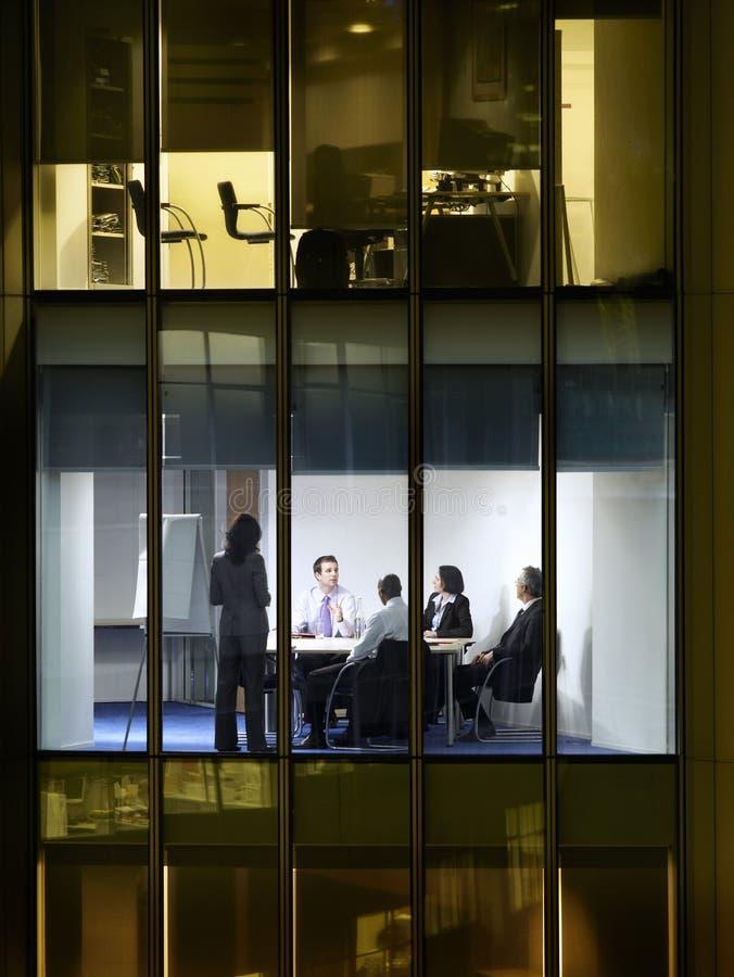 Hombres de negocios en sala de reunión en la noche imagenes de archivo